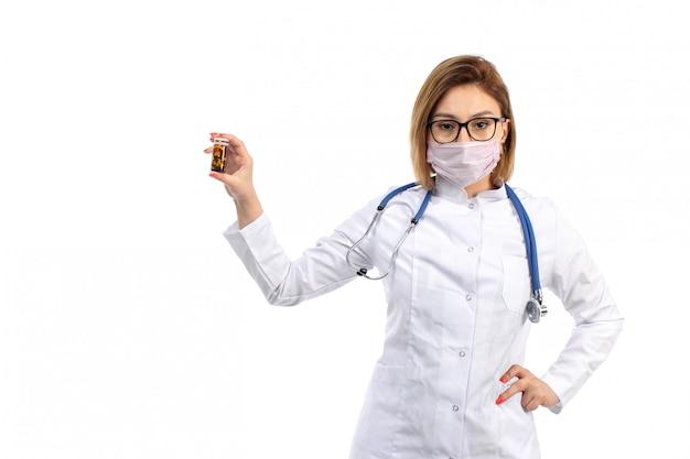 Uma vista frontal jovem médica no terno médico branco com estetoscópio usando máscara protetora branca segurando comprimidos no branco