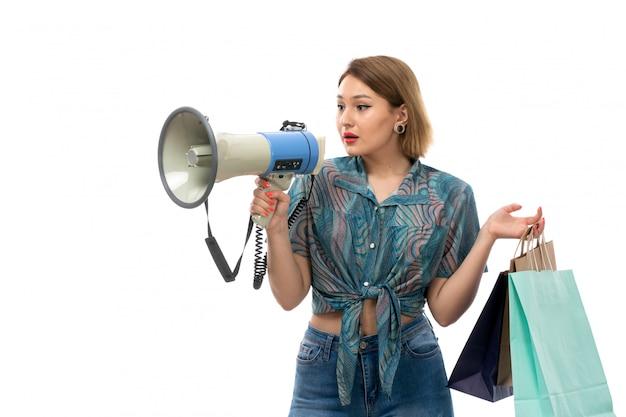 Uma vista frontal jovem mulher bonita blusa colorida jeans azul segurando pacotes de compras usando o megafone