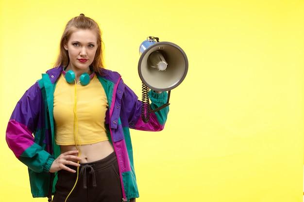 Uma vista frontal jovem mulher moderna em calças de camisa amarela e casaco colorido com fones de ouvido coloridos segurando megafone posando