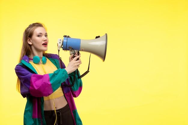 Uma vista frontal jovem mulher moderna em calças de camisa amarela e casaco colorido com fones de ouvido coloridos segurando o megafone
