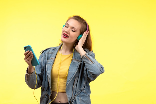 Uma vista frontal jovem mulher moderna em calças de camisa amarela e jaqueta jeans com fones de ouvido coloridos, ouvindo música posando