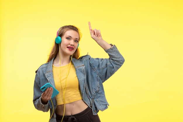 Uma vista frontal jovem mulher moderna em calças de camisa amarela e jaqueta jeans com fones de ouvido coloridos usando telefone posando
