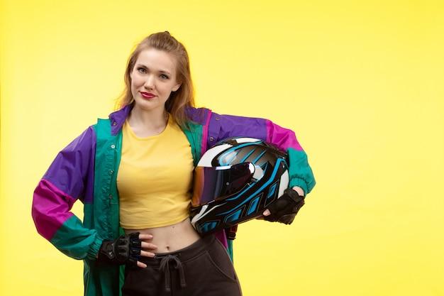 Uma vista frontal jovem mulher moderna na camisa amarela calça preta e casaco colorido segurando motocycle capacete posando