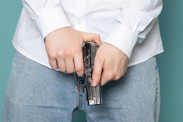 Uma vista frontal jovem segurando a arma em t-shirt branca sobre a mesa azul