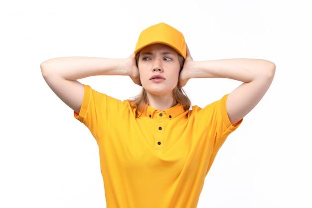 Uma vista frontal jovem trabalhadora do sexo feminino do serviço de entrega de comida com expressão perturbada no rosto cobrindo os ouvidos em branco