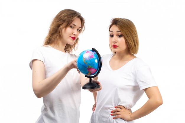 Uma vista frontal jovens senhoras em camisetas brancas, segurando um pequeno globo redondo no branco