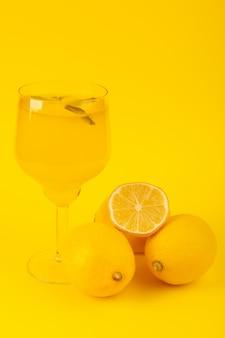 Uma vista frontal limões frescos amarelos frescos maduros inteiros e cortados com bebida de limão dentro de frutas de vidro isoladas sobre o fundo amarelo cor de frutas cítricas
