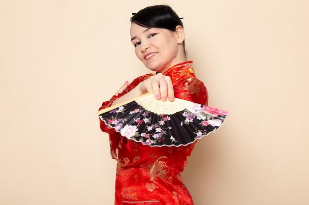 Uma vista frontal linda gueixa japonesa no tradicional vestido vermelho japonês com varas de cabelo posando segurando ventilador dobrável elegante sorrindo sobre a cerimônia de creme de fundo japão