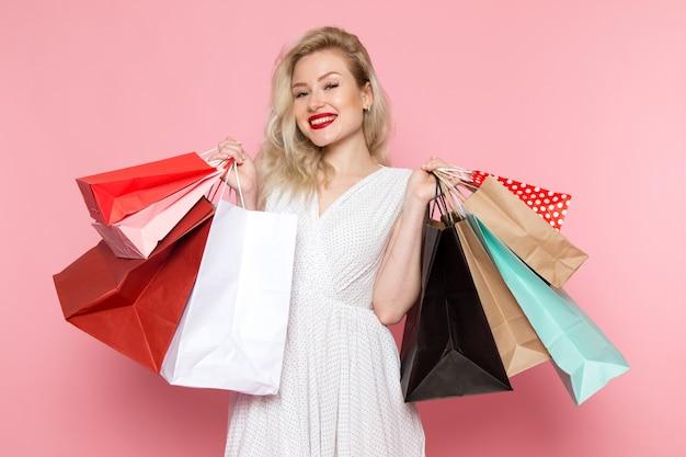 Uma vista frontal linda moça de vestido branco segurando pacotes de compras com sorriso no rosto