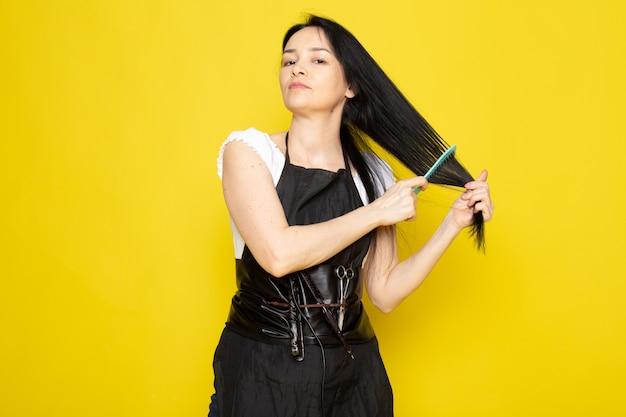 Uma vista frontal lindo cabeleireiro feminino na capa branca de camiseta preta com escovas com cabelo lavado, escovar o cabelo dela posando sobre o cabelo amarelo estilista de fundo amarelo