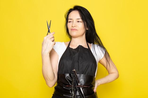 Uma vista frontal lindo cabeleireiro feminino na capa branca de camiseta preta com escovas com cabelo lavado, segurando uma tesoura posando no estilista de fundo amarelo cabelo de barbeiro