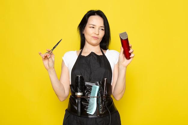 Uma vista frontal lindo cabeleireiro feminino na capa branca de camiseta preta com escovas com cabelos lavados, segurando uma tesoura e uma máquina posando no cabeleireiro estilista de fundo amarelo