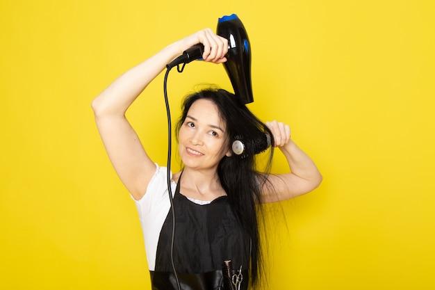 Uma vista frontal lindo cabeleireiro feminino na capa branca de camiseta preta com escovas com secagem de cabelo lavado, escovar o cabelo dela posando e sorrindo sobre o barbeiro estilista de fundo amarelo