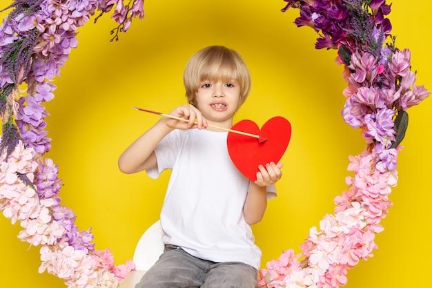 Uma vista frontal loira sorridente menino de camiseta branca, mantendo a forma do coração no chão amarelo