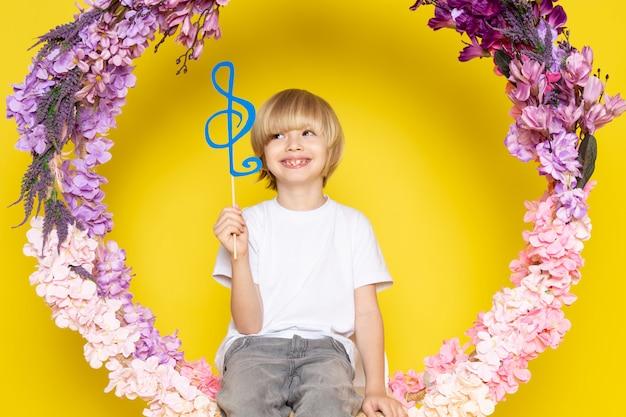 Uma vista frontal loira sorridente menino de camiseta branca, segurando a nota azul, sentado na flor feita ficar no espaço amarelo