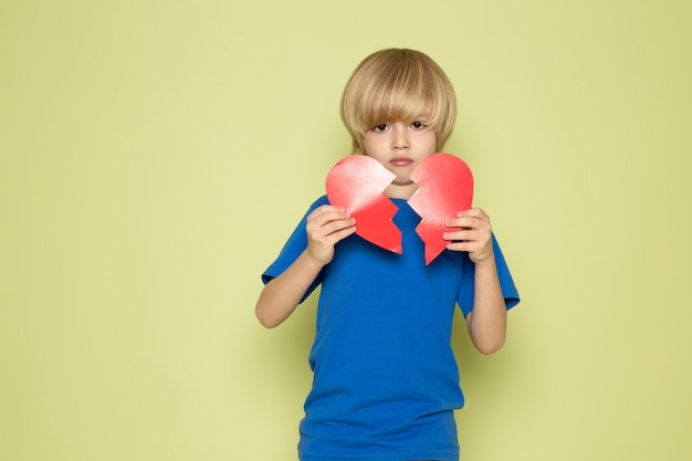 Uma vista frontal loiro garoto bonito em forma de coração rasgando doce adorável t-shirt azul no espaço colorido de pedra