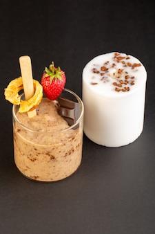 Uma vista frontal marrom choco sobremesa saboroso delicioso doce com café em pó barra de chocolate e morango isolado com vela branca sobre o fundo escuro doce doce sobremesa