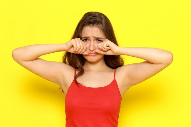 Uma vista frontal menina bonita camisa vermelha e calça jeans azul posando com expressão a chorar