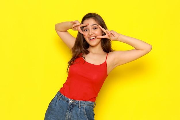 Uma vista frontal menina bonita camisa vermelha e calça jeans azul, posando com expressão engraçada
