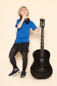 Uma vista frontal menino bonitinho na camiseta azul com fones de ouvido pretos, segurando o violão preto