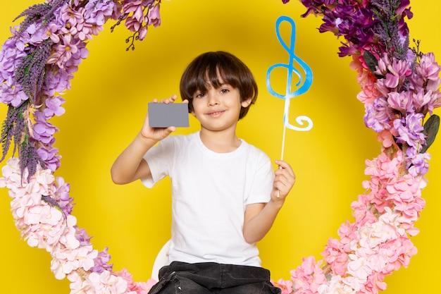 Uma vista frontal menino bonitinho na camiseta branca segurando o cartão cinza e o sinal azul no espaço amarelo