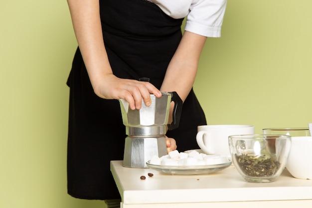 Uma vista frontal menino bonitinho preparando café beber em camiseta branca