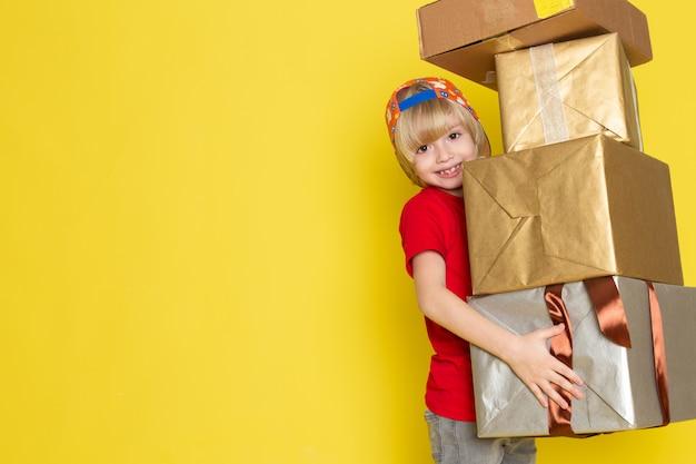 Uma vista frontal menino de boné vermelho de camiseta colorida e calça jeans cinza, segurando a caixa sobre o fundo amarelo