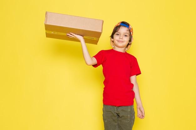 Uma vista frontal menino de boné vermelho de camiseta colorida e calças cáqui, segurando a caixa sobre o fundo amarelo