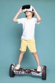 Uma vista frontal menino fofo adorável doce em t-shirt branca jogando vr em segway no espaço azul