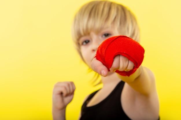Uma vista frontal menino loiro adorável boxe em camiseta preta na parede amarela