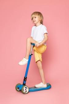 Uma vista frontal menino loiro cabelos adorável bonito em t-shirt branca andando de scooter no chão rosa