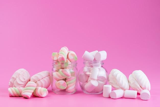 Uma vista frontal merengues e marshmallows doces e pegajosos, todos em bolo de biscoito doce de cor rosa
