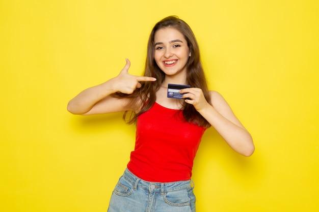 Uma vista frontal moça bonita camisa vermelha e calça jeans azul segurando o cartão com sorriso