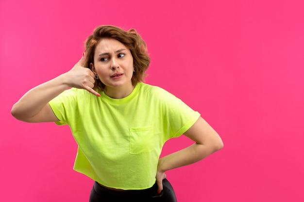 Uma vista frontal moça bonita em calças coloridas de camisa preta de ácido posando de conversa de telefone
