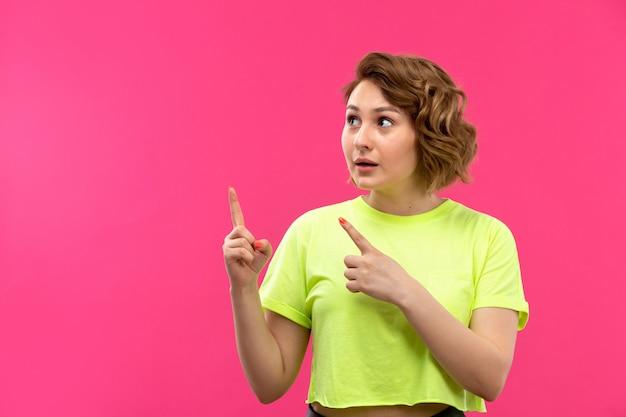 Uma vista frontal moça bonita em calças de camisa colorida de ácido posando de sonho