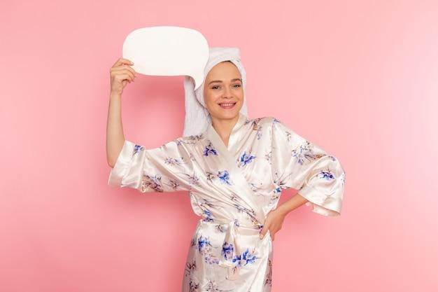 Uma vista frontal moça bonita em roupão segurando placa branca com sorriso no rosto