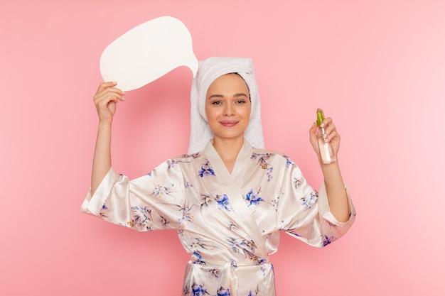 Uma vista frontal moça bonita em roupão segurando placa branca e spray