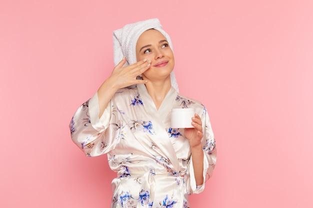 Uma vista frontal moça bonita em roupão usando um creme com sorriso no rosto