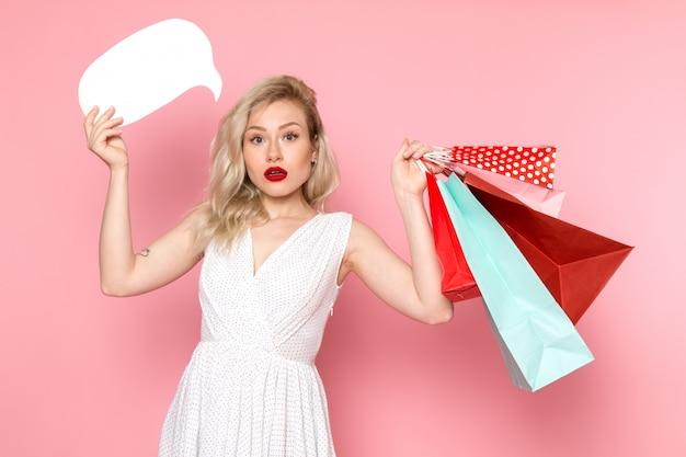Uma vista frontal moça bonita no vestido branco segurando pacotes de compras e placa branca