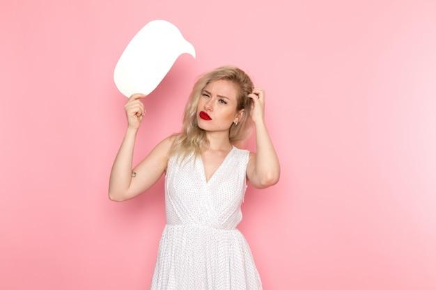 Uma vista frontal moça bonita no vestido branco segurando sinal whit com expressão confusa