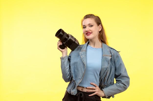 Uma vista frontal mulher moderna jovem de camisa azul calça preta e jean jacket posando expressão feliz sorrindo segurando a câmera fotográfica