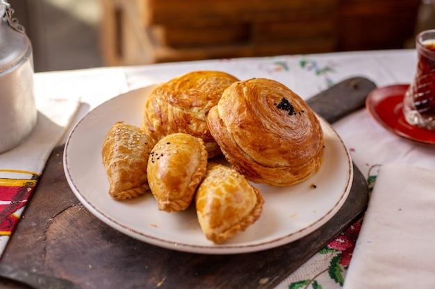 Uma vista frontal pastelaria assada qogals e outras padarias biscoitos hora do chá cerimônia de massa saborosa massa sobre a mesa
