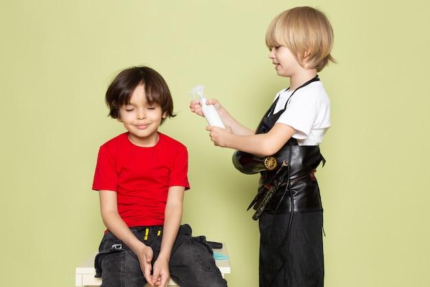 Uma vista frontal pequeno garoto adorável cabeleireiro bonito segurando spray