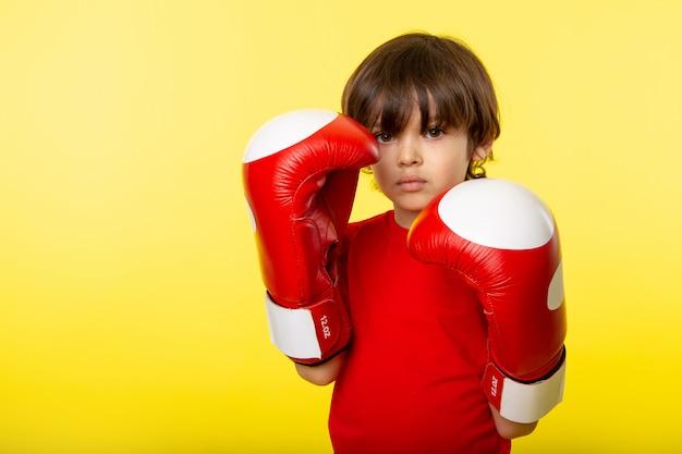 Uma vista frontal pequeno garoto bonito adorável em luvas de boxe azuis e t-shrit vermelho na parede amarela