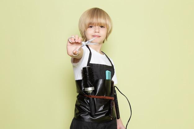 Uma vista frontal pequeno garoto loiro adorável cabeleireiro bonito com tesoura