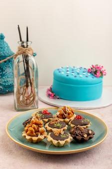 Uma vista frontal, pequenos bolos de chocolate dentro do prato com bolo de aniversário azul na mesa rosa, bolo doce de açúcar, biscoito de aniversário