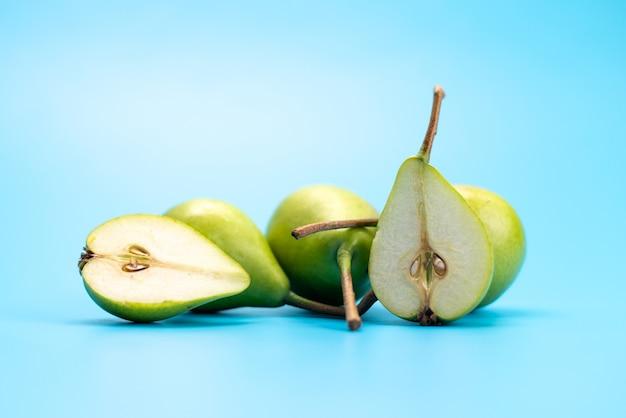 Uma vista frontal peras verdes frescas, doces e suaves no azul, cor de fruta madura