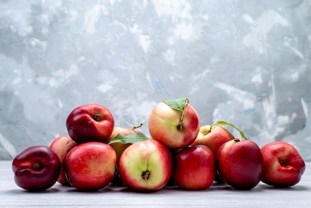 Uma vista frontal pêssegos frescos azedos e maduros no fundo branco cor da fruta fresca suculenta