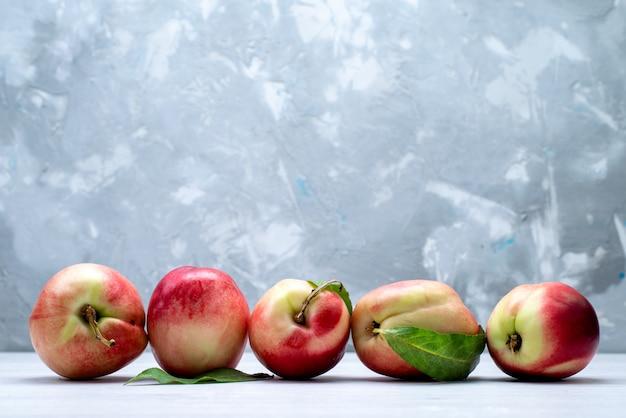 Uma vista frontal pêssegos frescos azedos e maduros no fundo branco cor de frutas frescas