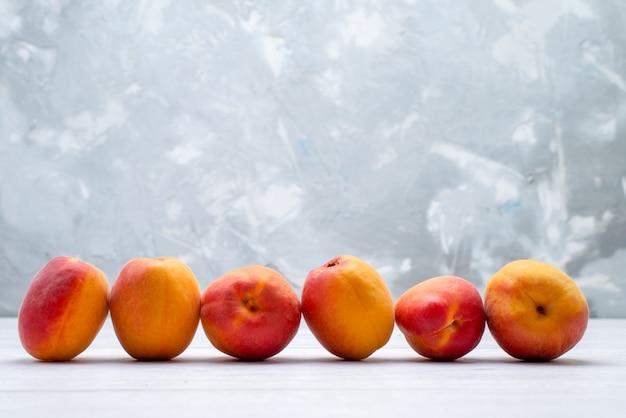 Uma vista frontal pêssegos frescos e suaves no fundo branco cor de frutas frescas e suculentas de verão